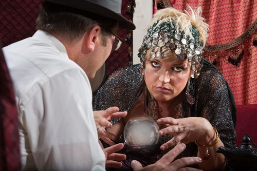 Serious Caucasian fortune teller reading a crystal ball